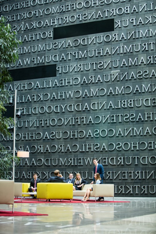 A high wall covered with line after line of large carved letters overlooks a neat seating area in the lobby