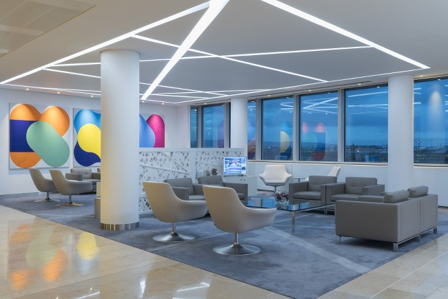 A reception area with plenty of seating, colourful art on the walls and windows looking out into evening light on the city