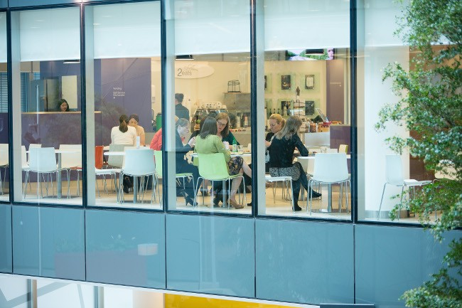 The view through the windows into the 2eats canteen where employees are enjoying their lunch