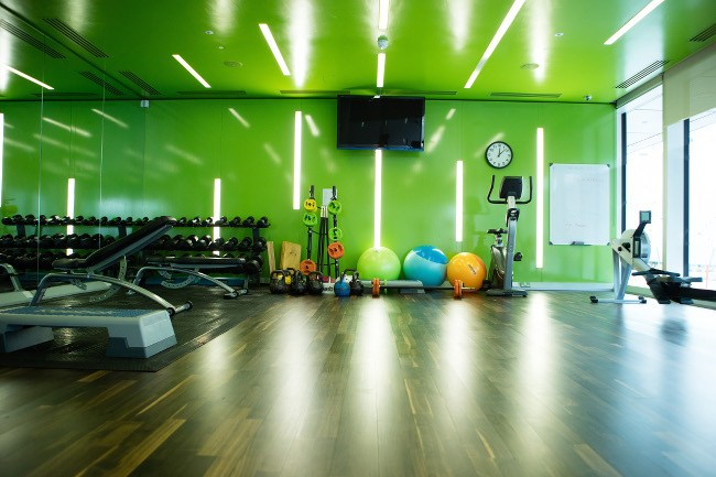 A gym with acid-green walls is stocked with equipment, weights, kettle-bells and colourful exercise balls