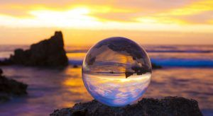 A crystal ball sitting on a beach up against the horizon. It will tell you what the future of work holds.