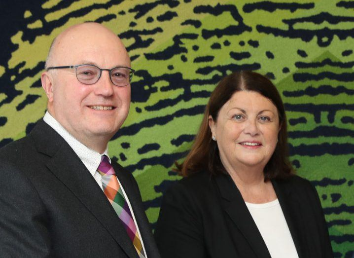 Prof Mark Ferguson and Máire Geoghegan-Quinn stand side by side smiling at the camera in front of a backdrop of a green fingerprint on black ground