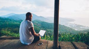 Man on laptop overlooking picturesque mountain range, remote working