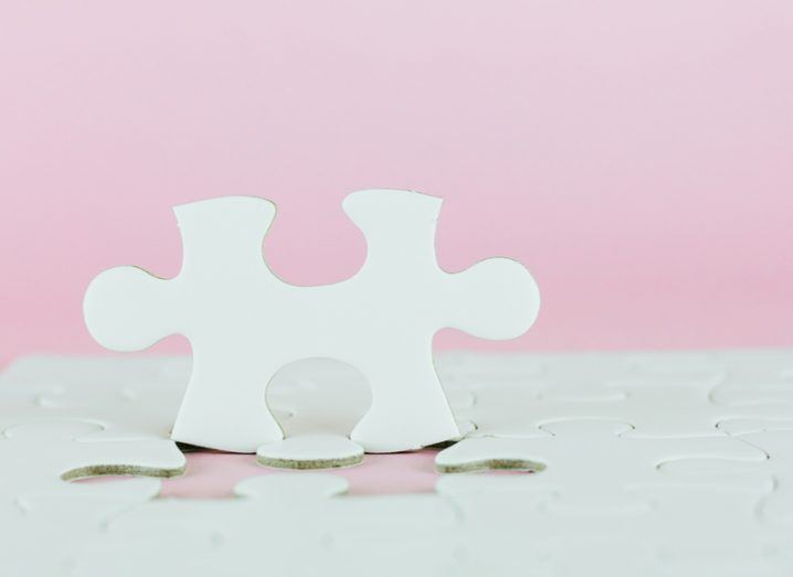 white jigsaw with missing piece on pink background