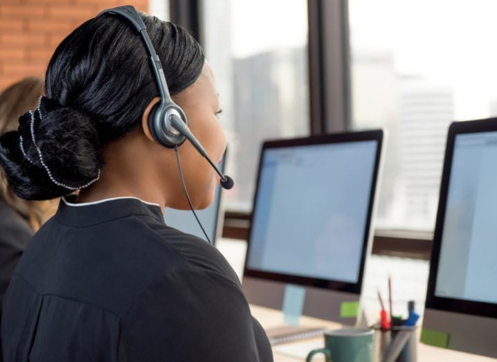 Call centre worker wearing a headset at a computer.