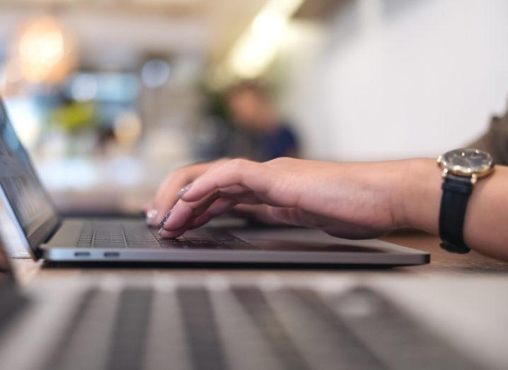 Woman typing on laptop. Human error is a massive cyber risk in the workplace