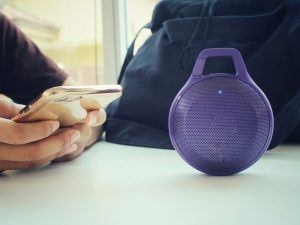 Bluetooth speaker beside a woman using a mobile phone
