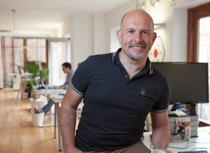 Graham Brierton wearing dark polo shirt casually sitting on a desk in an office.