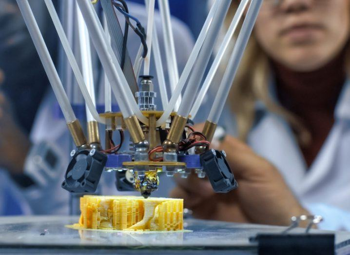 Scientists in lab coats gathered around a 3D printer watching the production of a yellow object in the lab.