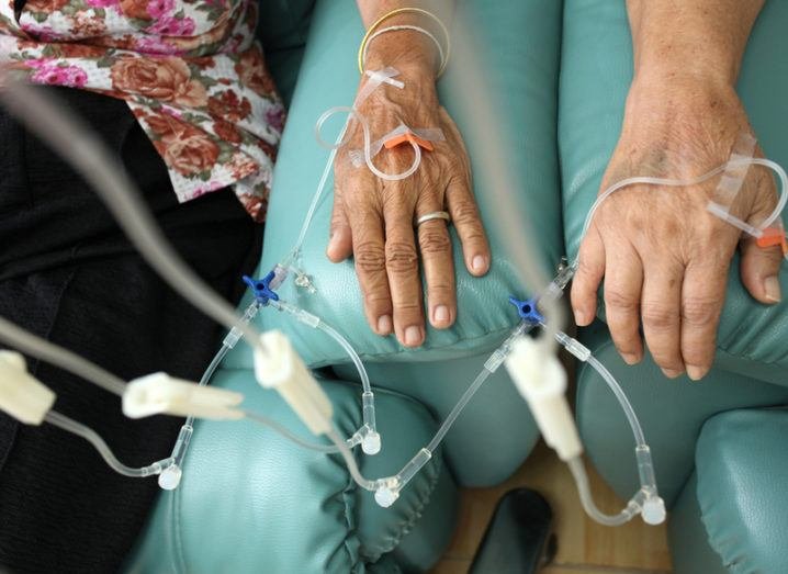 Two frail hands resting on blue couches as they receive chemotherapy