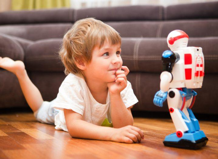 A child lying on the floor staring with interest at a toy robot.