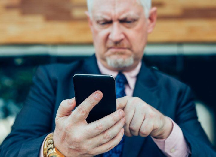 Confused middle-aged man in a suit looking at his mobile phone.
