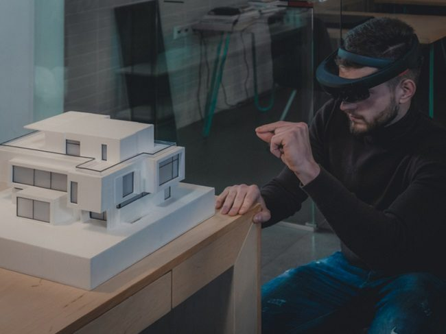 Bearded man wearing an augmented reality headset looking at a 3D model of a house.