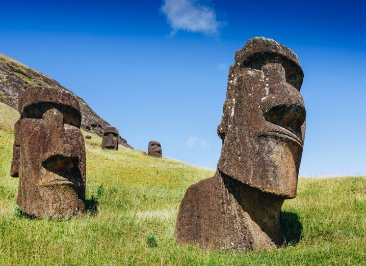 Stone Easter Island heads on green grass with blue sky overhead.