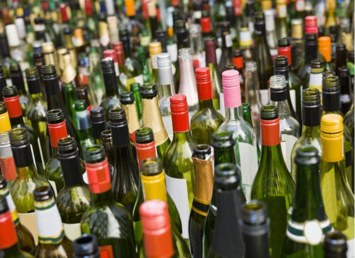 Collection of multi-coloured wine bottles going as far back as you can see.