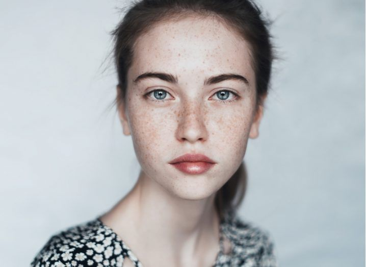 Close-up of a young white woman's face against a grey wall.
