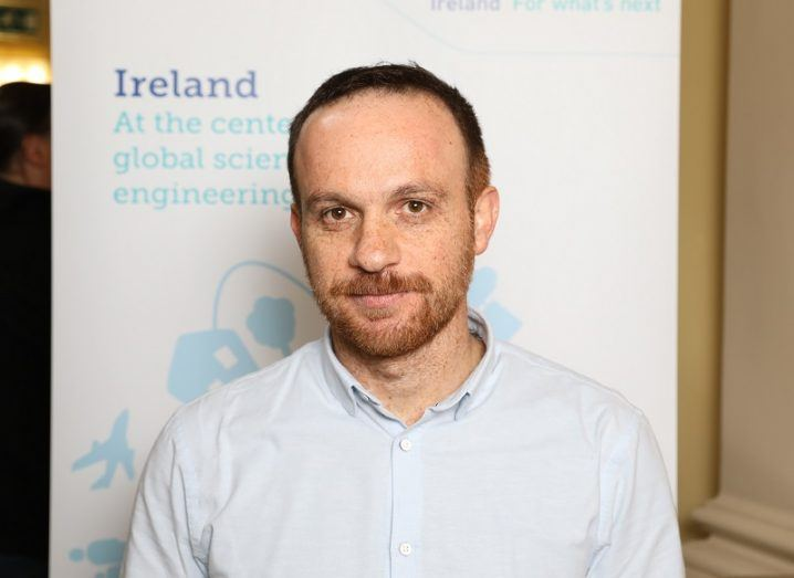 George Iosifidis standing in front of a Science Foundation Ireland backdrop.