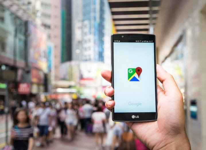 Hand holding an Android phone on a busy street in Hong Kong with Google Maps app open.