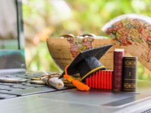 Mortar board on top of a laptop