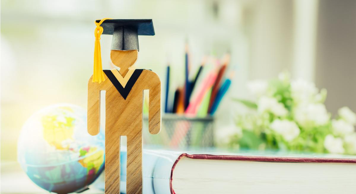 A wooden figurine with a graduation cap on in front of a book, some stationary and a globe wondering about what jobs for graduates exist