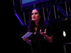 Susan McPherson in a black dress on stage at Inspirefest holding note-cards for her presentation on corporate responsibility