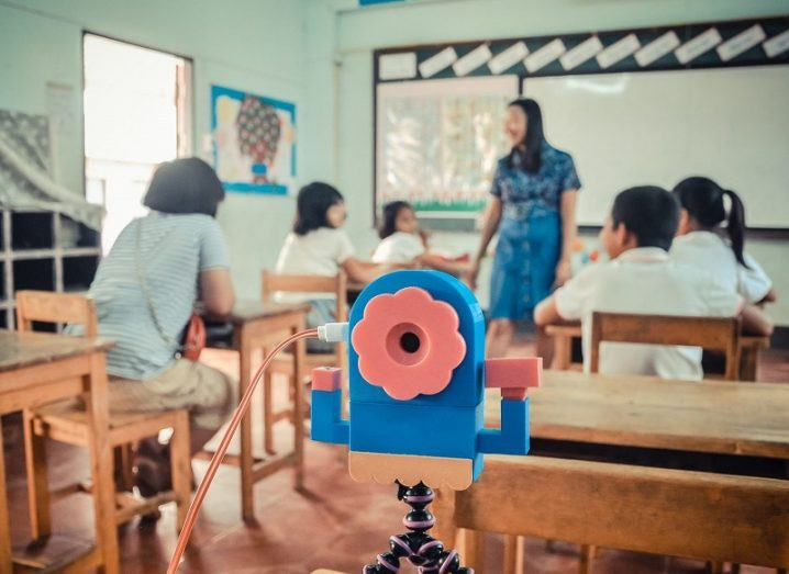 A pink and blue IoT device in centre frame with a teacher and pupils in the background.