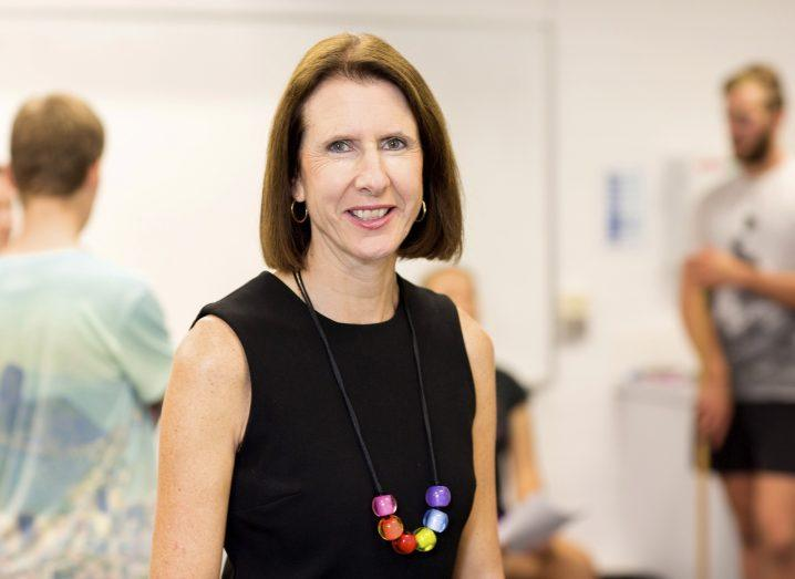 Professor Julie Steele smiling in her lab wearing a black dress with multi-coloured necklace.