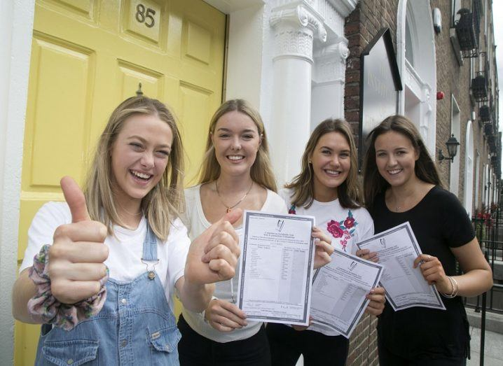 Four smiling students holding their Leaving Cert exam results beside a yellow door.