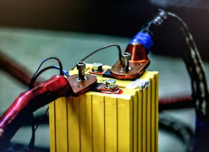 A red cable and a blue cable connected to a yellow lithium battery block used for electric vehicles.