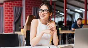 Young professional woman sitting at a desk in her new job and smiling