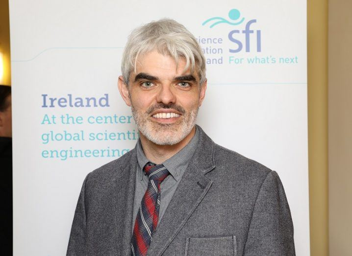 Grey-haired bearded man wearing grey shirt and jacket posing for a photo in front of a white backdrop with SFI logo.
