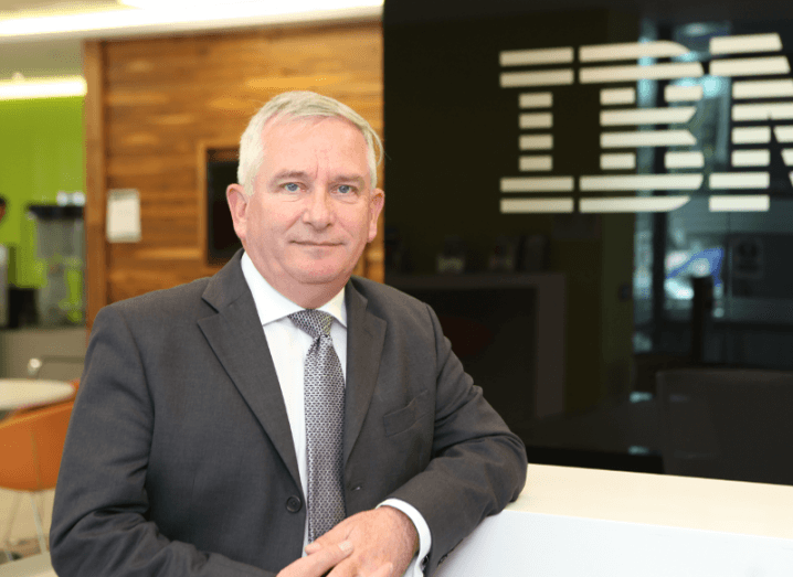 Paul Farrell smiling wearing a suit with the IBM logo in the background.