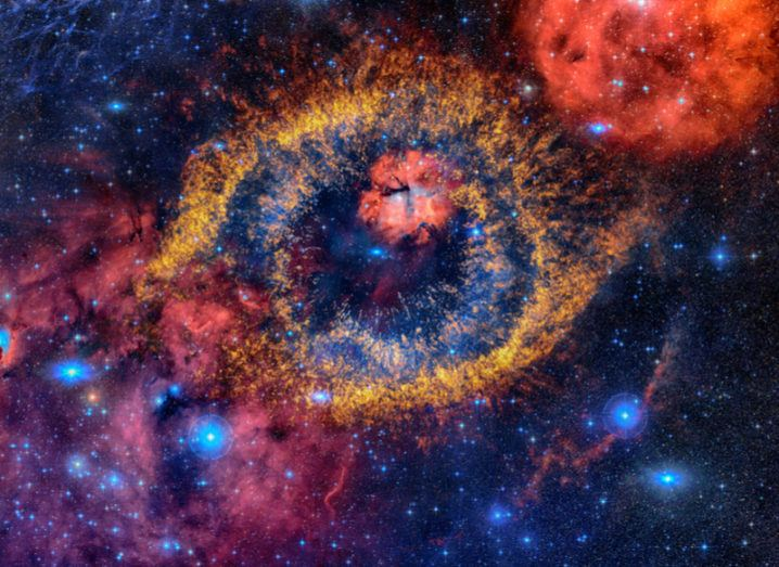 A nebula in space with an orange outer ring and blue inner rings, similar in shape to a human eye.