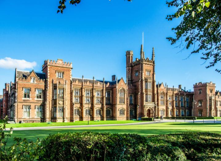 A backdrop of a clear-blue sky with a green lawn and the front of Queen's University Belfast.