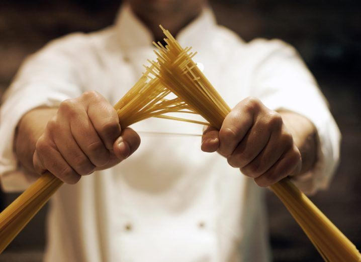 Chef in a white jacket holding two bundles of spaghetti, one in each hand as if he is breaking it in two.