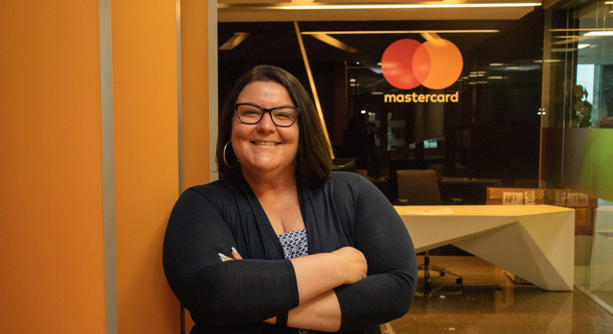 Tammy Hawkins, a smiling brunette woman with glasses standing in the Mastercard offices.