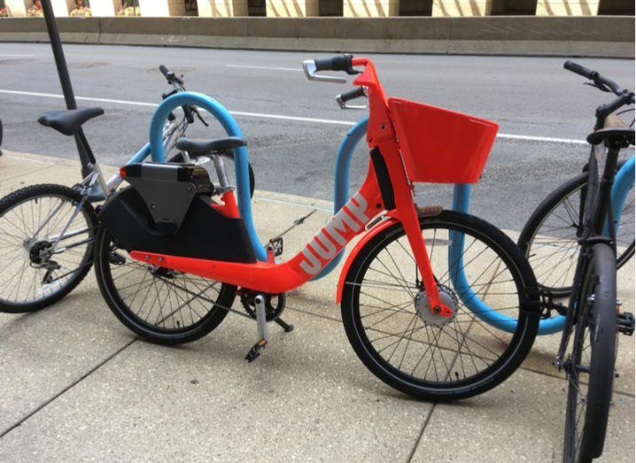 A red Uber Jump ride-sharing bicycle locked to a blue railing on the side of a street.
