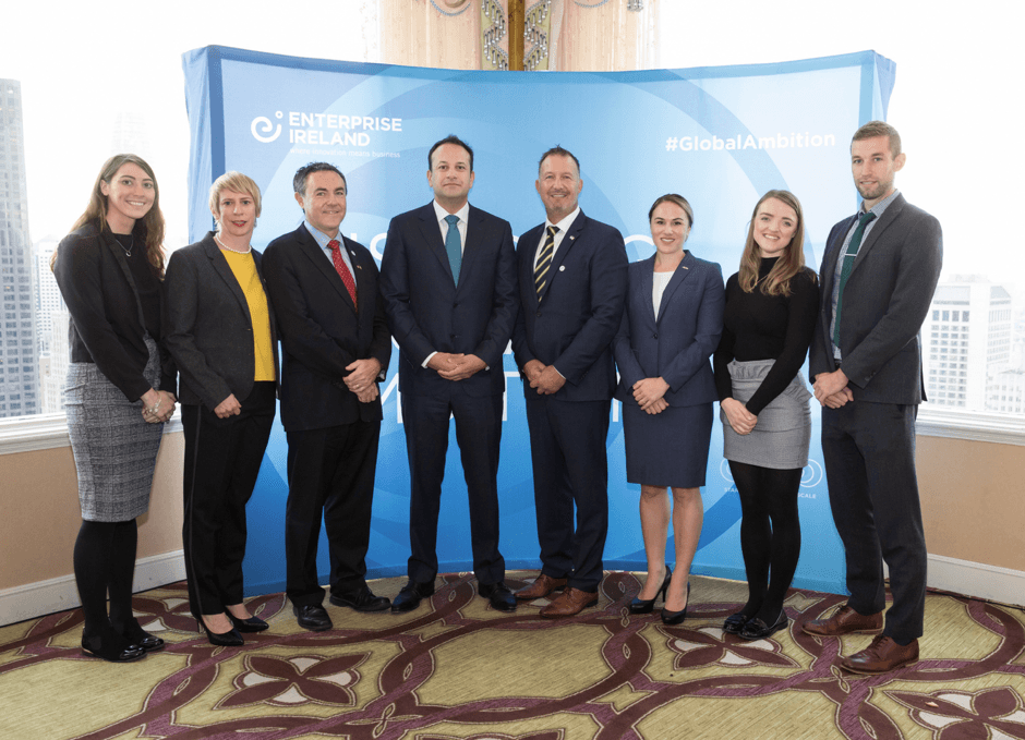 Leo Varadkar stands at the centre of a row of people in business attire, standing in front of an Enterprise Ireland backdrop.