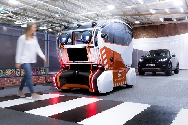 A self-driving car with human-like eyes watching a woman at a pedestrian crossing.