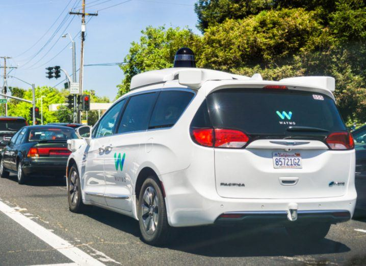 A white Waymo test vehicle waiting in traffic.