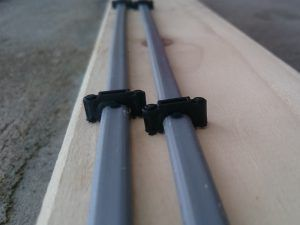cables fastened with black plastic clip on wooden board