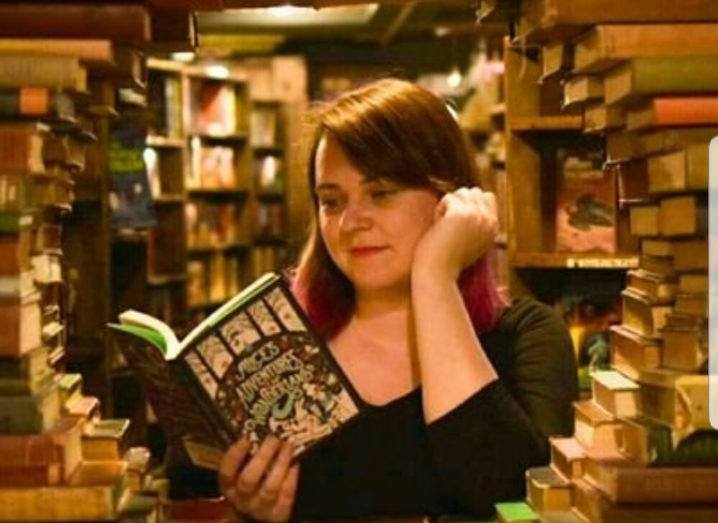 Sexuality studies researcher Caroline West is framed by a circle of books, reading Alice's Adventures in Wonderland