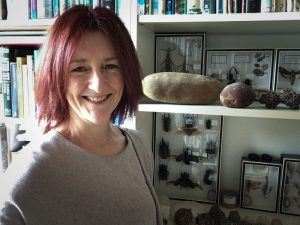 Colette Kinsella stands smiling in front of a bookcase packed with books, rocks, shells and insect displays