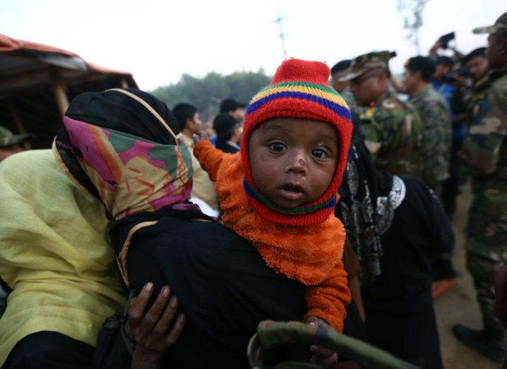 A Rohingya baby in a carrier on someone's back at a refugee camp in Bangladesh.