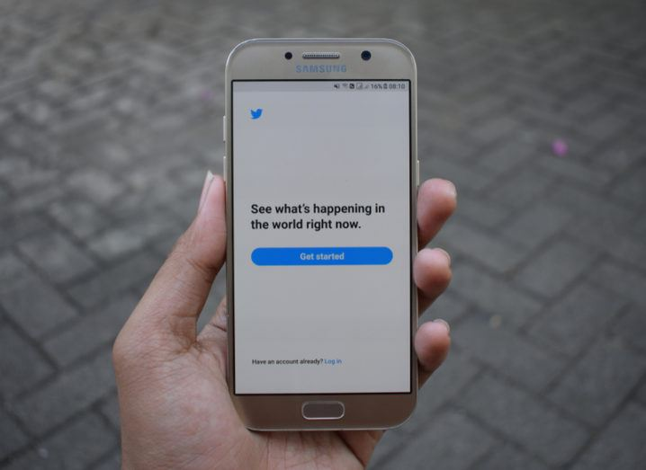 Hand holding a Samsung phone with the Twitter app open.