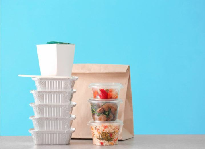 Two stacks of takeaway containers filled with different food in front of a brown paper bag and sky blue background.