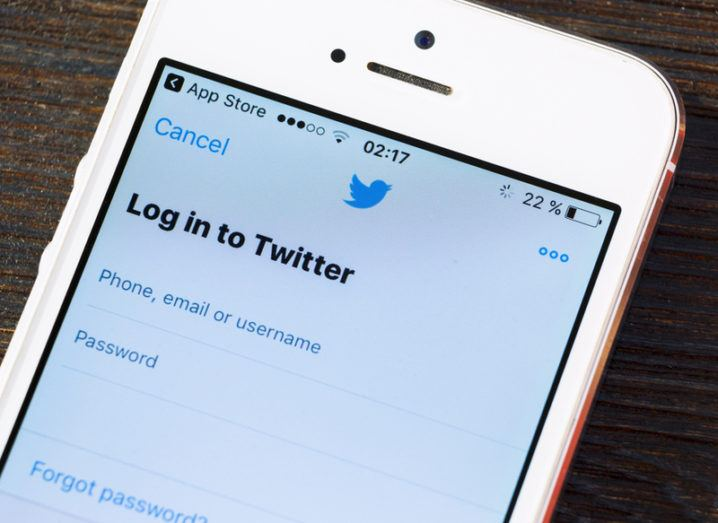 Twitter login screen on a white iPhone SE.