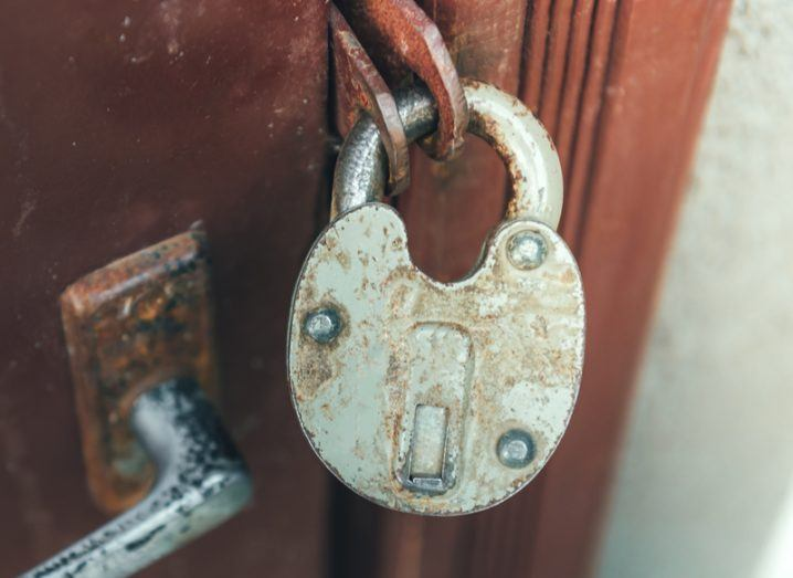 An old rusty padlock keeping a metal door closed. Data protection concept.