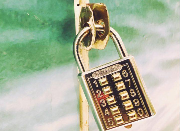 Gold combination lock holding a green door closed.