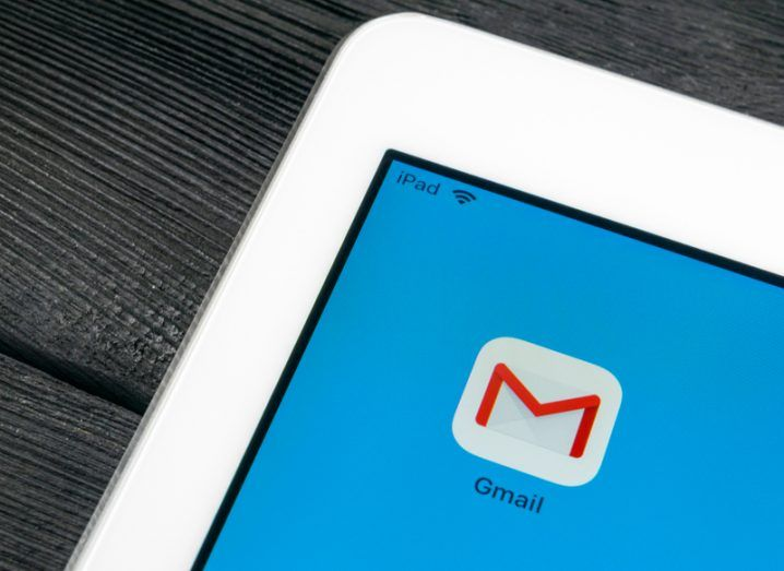 Gmail app icon on an iPad with a blue background, sitting on a dark wood surface.